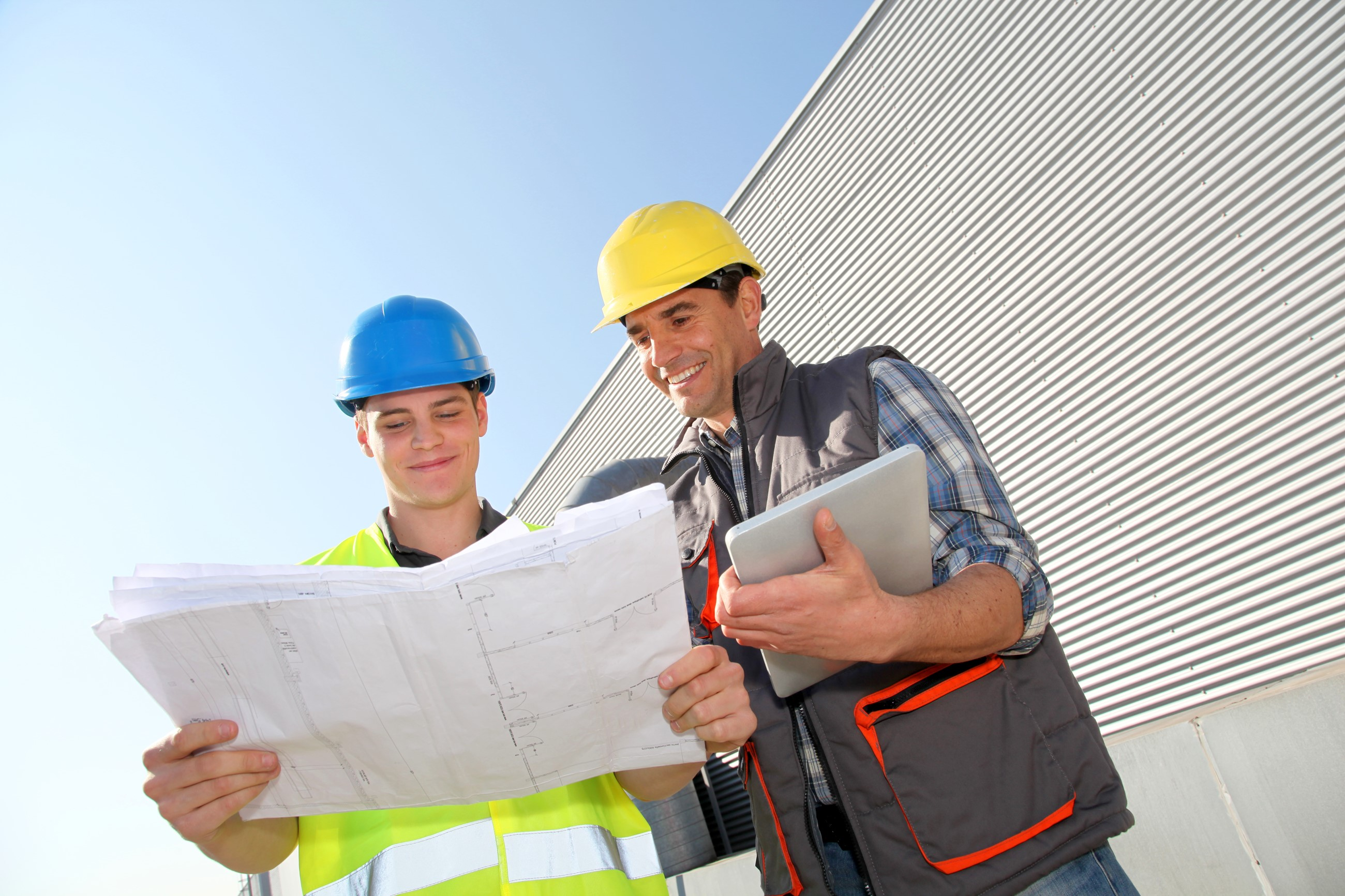 2 people in hard hats viewing planning documents