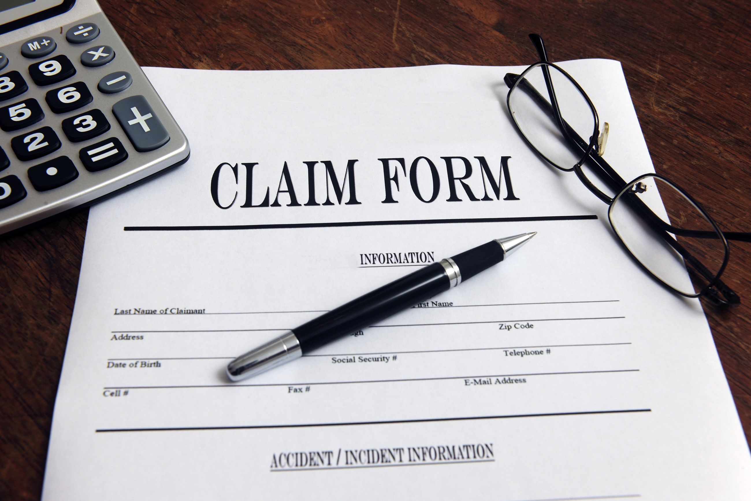 Claim Form with pen, calculator and eyeglasses on top of desk